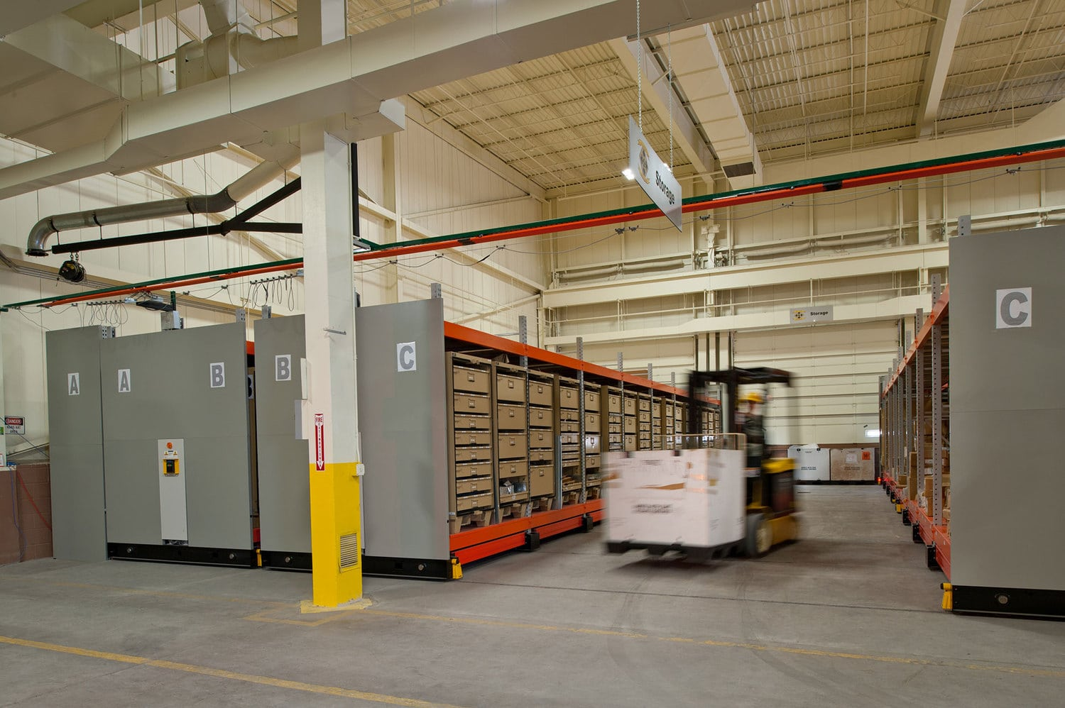 Forklift moving supplies from ActivRAC industrial mobile shelving system at Fort Carson