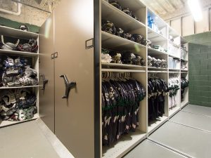 Jerseys and sports gear stored on mobile shelving