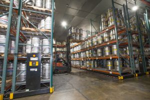 Kegs stored on compact shelving in warehouse