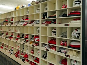 Football helmets and gear stored on shelving at University of Louisville